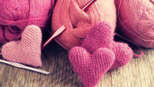 Crochet pink hearts and yarn on wooden background.